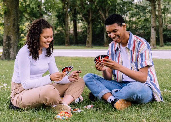 man-and-woman-sitting-on-grass-playing-cards-2981571